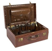 A crocodile skin fitted dressing case containing engine turned silver backed hair bushes, bottles etc./see illustration