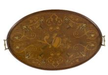 An Edwardian mahogany oval tray inlaid musical instruments, scrolls, etc., with brass handles, 68cm wide
