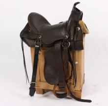 A Western saddle with tooled decoration and stirrups