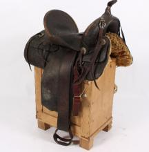 A Western saddle with tooled decoration and iron stirrups