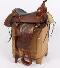 A modern Western saddle with tooled decoration, leather covered stirrups and canvas cover