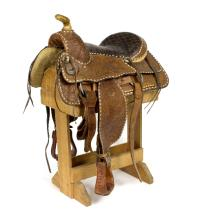 A Western saddle with tooled decoration, leather covered stirrups and white metal mount to the saddle horn, numbered 1959, with canvas cover, on a wooden saddle horse/see illustration