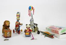 A group of tinplate clockwork toys comprising a pedalling elephant balancing a ball, a pedaling duck with a rotating hat, a drumming monkey, a dancing panda and a boxed moving crocodile