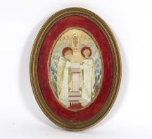 An embroidered oval panel of two angels and a vision of The Host, circa 1900, 25cm x 16cm