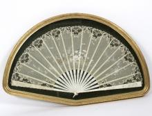 A late 19th Century painted French fan with lace leaf and ivory sticks and guards, set in a glazed frame with gilded border, overall 66cm wide