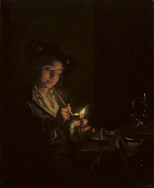 A candlelit interior with a young man seated at a table, lighting his pipe