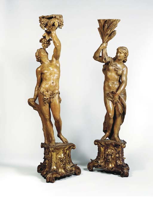 A PAIR OF PARCEL-GILT CARVED WOOD TORCHERES OF BACCHUS AND CERES AS AUTUMN AND SUMMER
