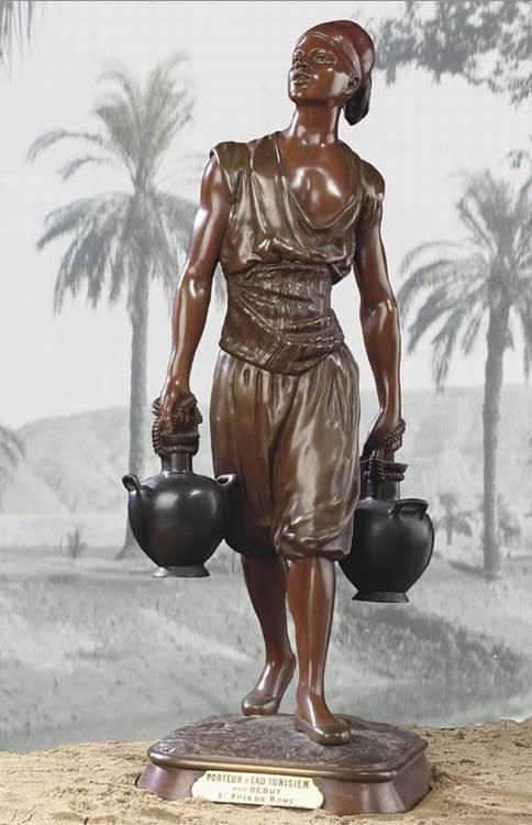 A brown and green patinated bronze figure Le porteur d'eau tunisien