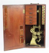 Antique monocular microscope in fitted case, opening to five drawers, containing eye pieces, and (7) objectives in canisters, some r...