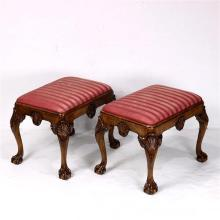 Pair of Chippendale style ottomans, having an upholstered seat, with an apron having a carved shell medallion, the knees accented wi...