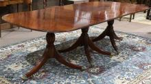 Regency style triple pedestal dining table, the top having rounded corners, with a banded inlaid border, supported by a pedestal bas...