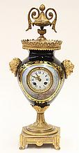 Sevres style porcelain clock, of urn form, having ormolu mounts with a flame finial above a scalloped and pierced gallery surmountin...