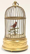 French caged bird automaton, executed in gilt brass, depicting a red bird on a perch with vines inside a brass dome wire cage, the w...