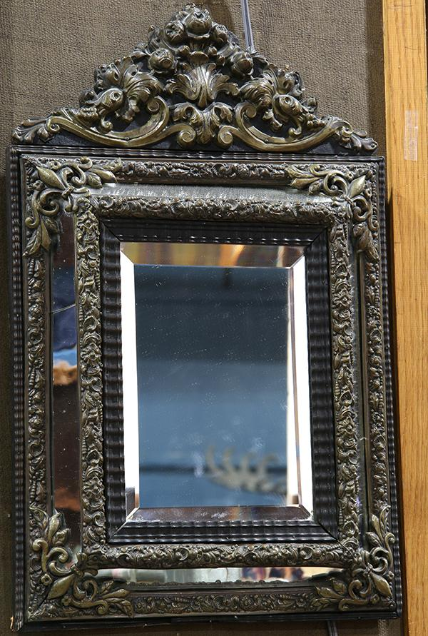 French Neo-Classical style wall mirror mounted with floral repousse brass accents, 20