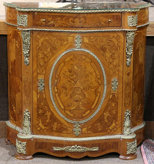 Continental Neoclassical style inlaid commode, having a shaped top, above the gilt mounted case with a single drawer, surmounting a...