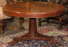 English Regency mahogany center table, 19th century, having a circular bookmatched top, above the columnar standard and rising on a ...