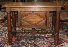 Jacobean style oak low table, 19th cenury, having a rectangular top above a single paneled drawer, and rising on turned legs, 22