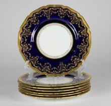 (lot of 7) Royal Doulton cabinet plates, each having a raised gilt rim continuing to a cobalt border, centering a cream ground, 10