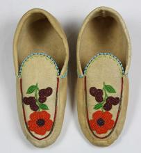 Native American beaded moccasins , 20th Century, accented with polychrome orange, green, and red floral sprays, 11
