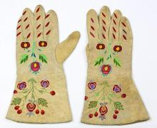 Native American Indian beaded gauntlets, 20th Century, the suede gloves having polychrome floral embroidery in the Art Nouveau style...