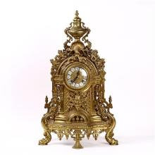 Rococo Revival style brass mantle clock, the round face with enamel Roman numerals, rising on a footed base, 24