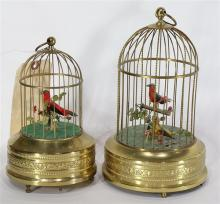 (lot of 2) Musical mechanical automaton birdcages, each with a single red finch housed in a gilt metal cage, circa 1910, 9
