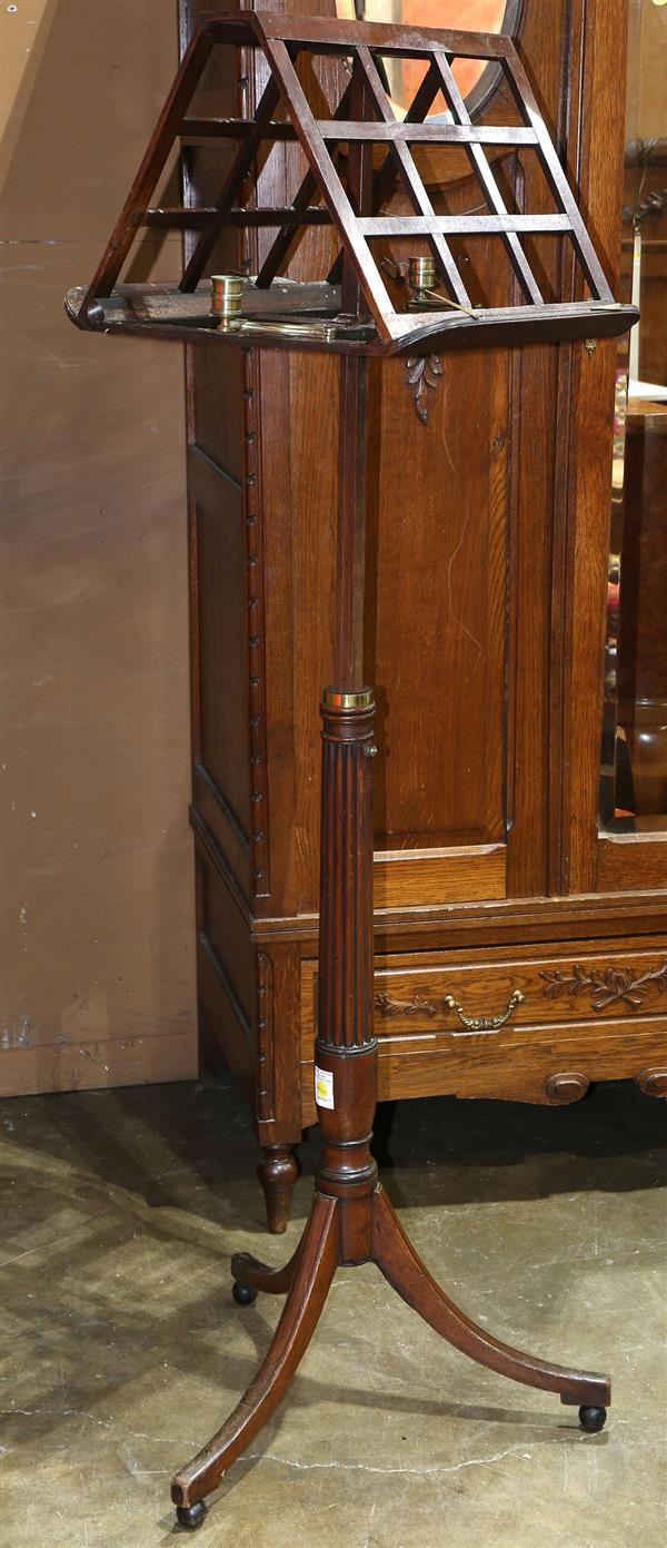 Edwardian music stand, having two slatted props, flanked by adjustable brass single light candle holders, above the turned adjustabl...