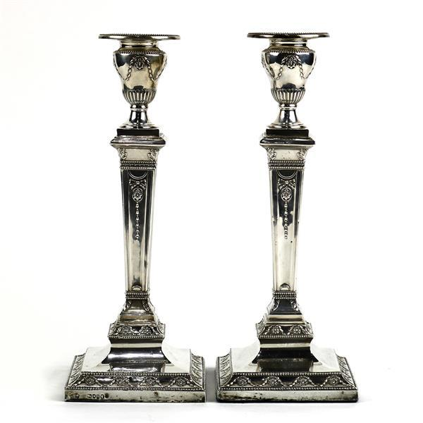 Pair of Victorian Neo-Classical style sterling silver weighted candle holders, London, circa 1883, the circular removable bobeche ac...