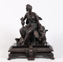 PATINATED METAL AND MARBLE SCULPTURE OF A SEATED FEMALE SUBJECT WITH CUPID
