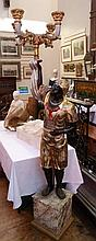 A carved and painted blackamoor, standing holding