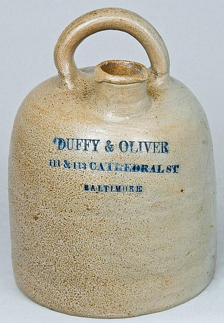 Very Rare Rainbow-Handled Stoneware Advertising Jug, Baltimore, MD origin, circa 1870, dome-shaped jug with wheel-thrown and applied spout and horizontal handle on top, impressed with the cobalt-highlighted advertising