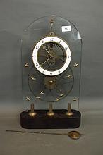 A large brass and glass mantle clock with open