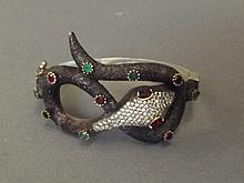 A silver, ruby and emerald set bangle in the form