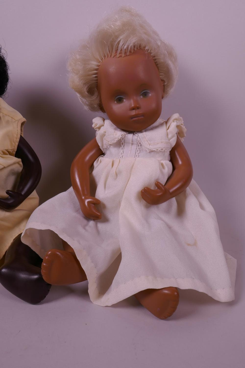 Three Sasha dolls including a black baby doll with pink lips, blue