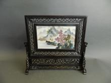 A Chinese porcelain rotating table screen with enamelled landscape decoration, mounted in a carved and pierced hardwood frame, 16