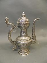 An Indian mixed metal ewer with scrolling repoussé decoration and dragon handle and spout, 14