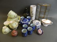 A quantity of decorative pottery and porcelain including two part tea services, and a glass display case
