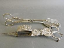 A pair of silver plated candle snuffers with ornate cast decoration, and a pair of silver plated asparagus tongs, 8½