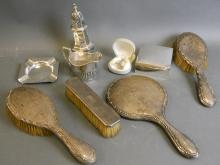 A Hallmarked silver sugar sifter, Chester 1901, 84g, a Hallmarked silver cream jug, 48g, Hallmarked silver cigarette box, Hallmarked silver ashtray, 1952/53 by Mappin & Webb, 62g, Hallmarked silver tooth fairy bell, Hallmarked silver backed dressing mirror, and three Hallmarked silver backed brushes