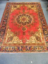 A Persian Heriz carpet with central floral medallion decoration on a red field within a blue ground border, 114