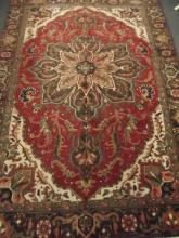 A Persian Tabriz carpet with floral design on a red field within a black ground border, 104