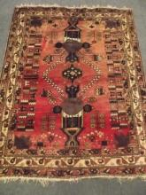 A Persian hand knotted wool carpet with stylised geometric patterns on a tomato coloured field, 58