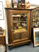 A French carved oak display cabinet with decorative sign written door and mirrored back, 43