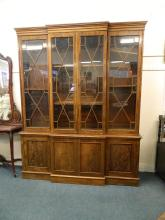 A C19th figured mahogany breakfront four door bookcase, in two sections, with astragal glazed upper section over four cupboards, on a plinth base, 78
