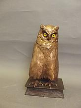 A large bronze figure of an owl standing on a book