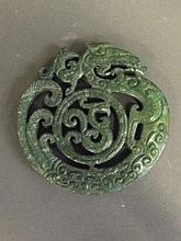 A Chinese circular hardstone pendant with pierced