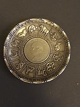 A Chinese white metal coin dish with relief zodiac