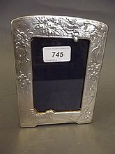 A silver photo frame decorated with a cockerel and