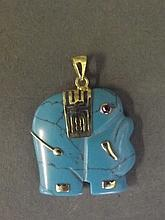 A turquoise stone and yellow metal pendant carved