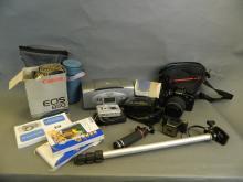 A collection of cameras and lenses including a Canon EOS 850 SLR with a Sigma 70mm lens, Canon Speelite 200E, Canon Snappy EZ, Ensign Midget model 22, Casio Exilim, HP Photosmart 100 photograph printer, manuals and spare cases